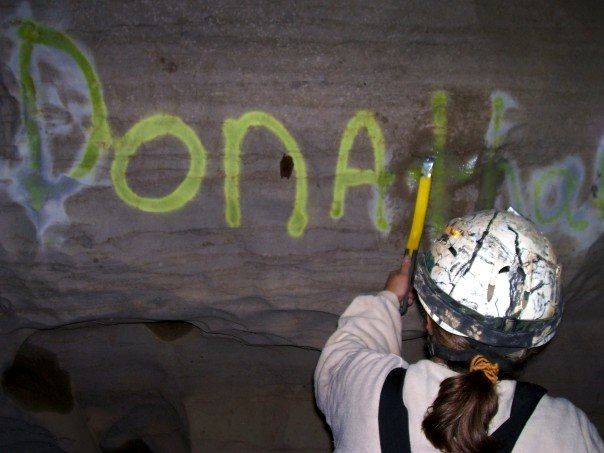 Cleaning cave graffiti.